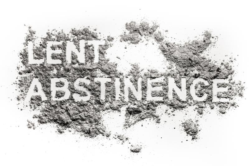 Lent abstinence word text written in ash. Sand or dust as fasting and penance time before easter and ash wednesday holiday concept stock photos