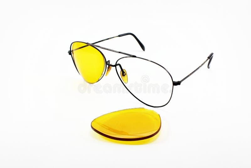 Lente amarela quebrada dos óculos de sol no fundo branco fotografia de stock royalty free