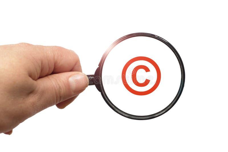 Lente d'ingrandimento a disposizione e una parola del copyright sui precedenti bianchi immagine stock libera da diritti