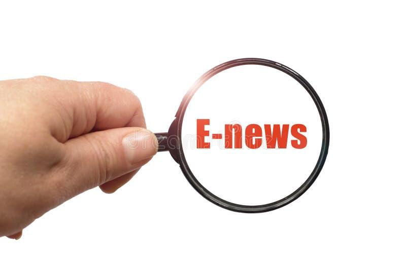 Lente d'ingrandimento a disposizione e una parola di E-notizie sui precedenti bianchi fotografie stock