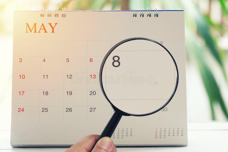 Lente d'ingrandimento a disposizione sul calendario potete guardare l'ottavo giorno di immagine stock libera da diritti