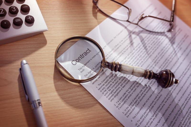 Lente d'ingrandimento su un contratto legale immagini stock libere da diritti