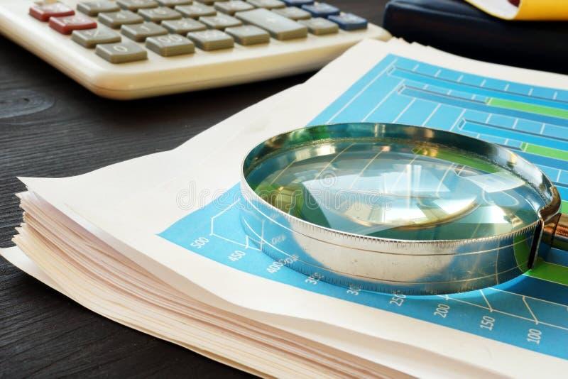 Lente d'ingrandimento sui documenti con le statistiche d'impresa Analisi dei dati finanziaria immagine stock libera da diritti