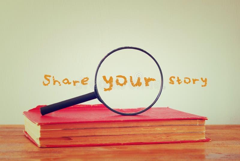 Lente d'ingrandimento, vecchio libro con la parte di frase la vostra storia Immagine filtrata fotografie stock
