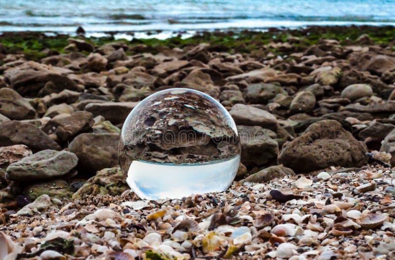 A lente da bola de vidro encontra-se na areia da costa de mar fotos de stock royalty free