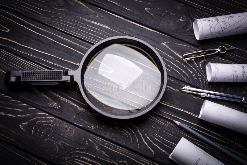 Lente de aumento, compassos e rolos do desenho em um fundo de madeira preto foto de stock royalty free