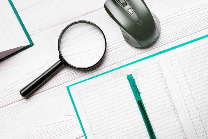 Lente de aumento e caderno com pena de esferográfica e rato do computador em uma tabela de madeira branca como um conceito da bus foto de stock