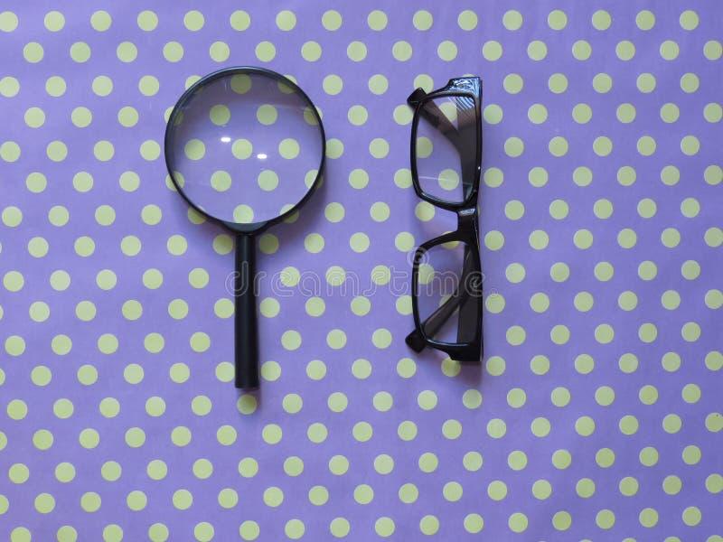 Lente de aumento de leitura à mão, lupa, um par de vidros com quadro preto no fundo amalucado manchado foto de stock