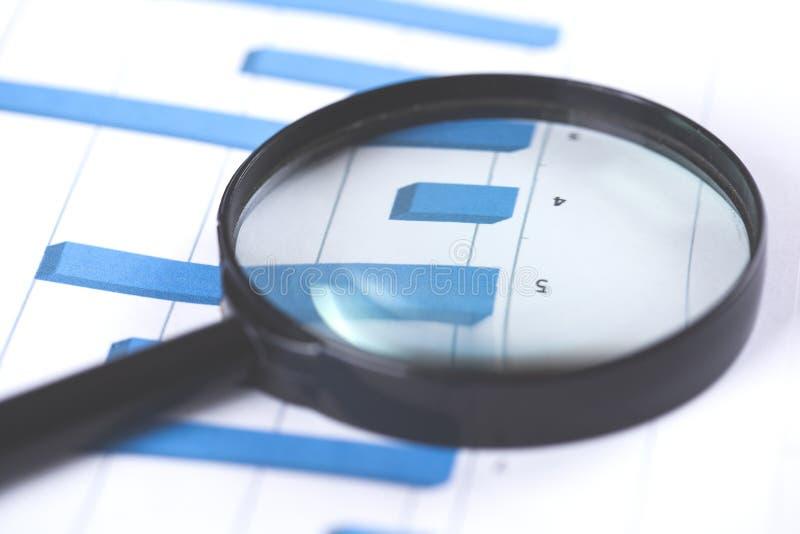 Lente de aumento no fundo do papel de gráfico da finança fotografia de stock royalty free