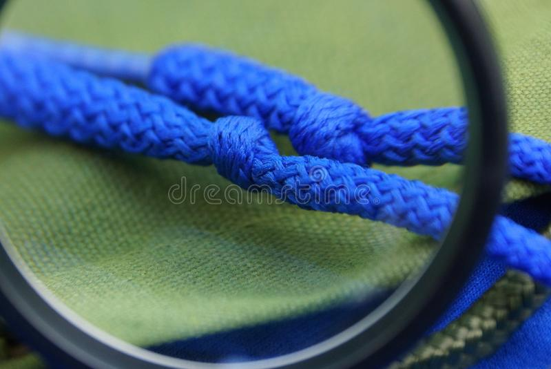 a lente de aumento preta amplia dois laços azuis connosco na matéria verde foto de stock royalty free