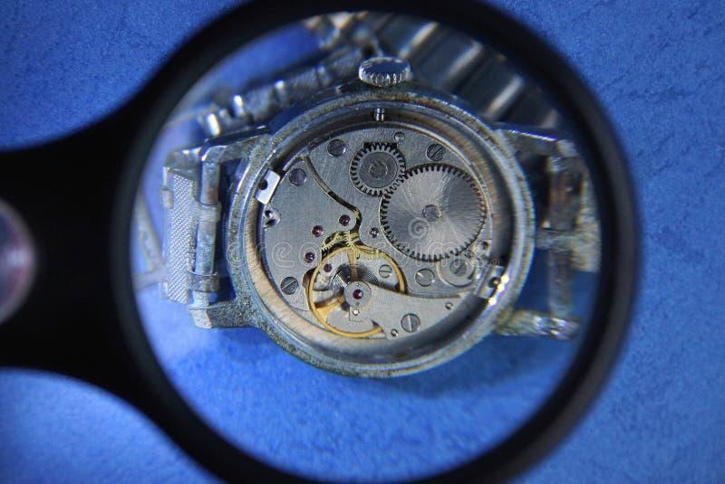 A lente de aumento preta aumenta o mecanismo aberto do relógio fotos de stock royalty free