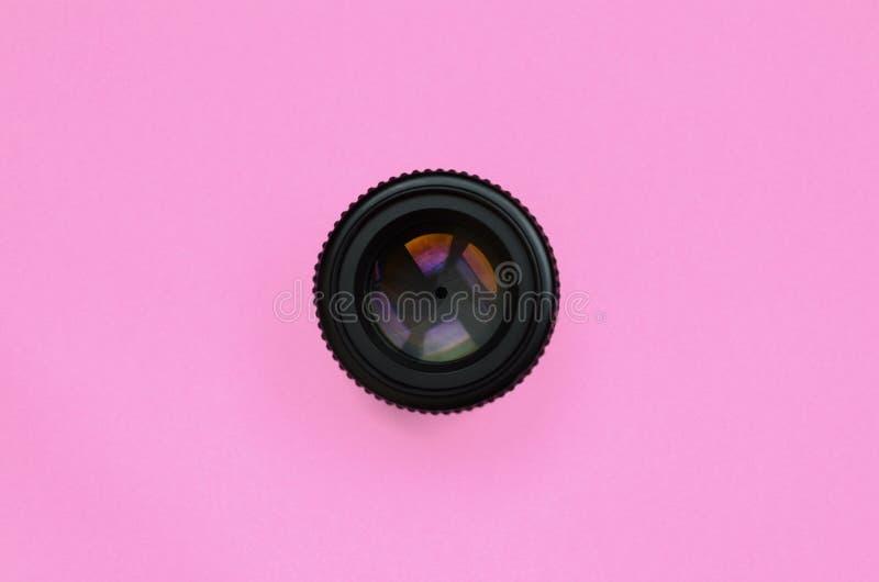 Lente de cámara con una mentira cerrada de la abertura en el fondo de la textura del papel rosado en colores pastel del color de  imagen de archivo libre de regalías