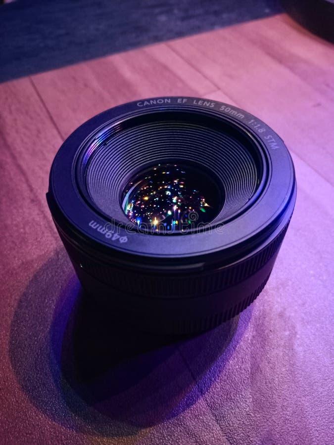 Lente de cámara del canon con la reflexión de la luz shrimmering que pone en la tabla imagen de archivo libre de regalías