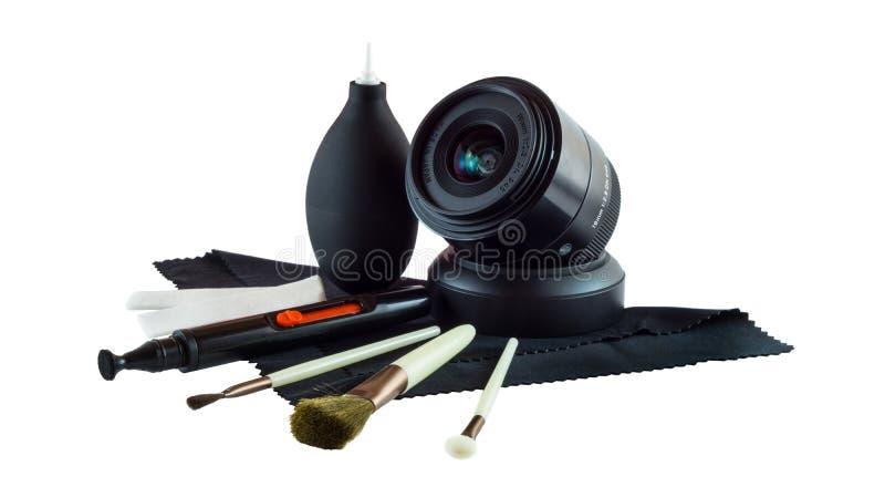 Lente de cámara de la foto y equipo de limpieza de la lente aislado en el fondo blanco imagen de archivo libre de regalías
