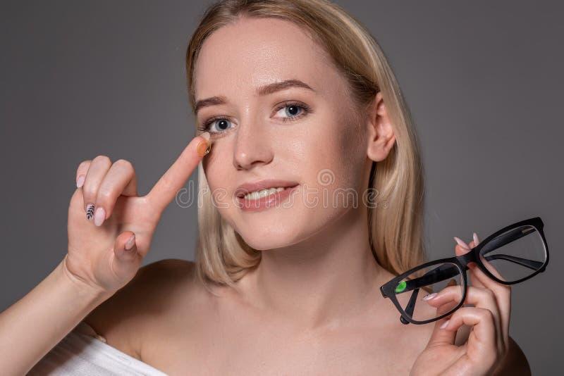 Lente de contato loura nova da terra arrendada da mulher no dedo na frente de sua cara e realizar em sua outra mão uns vidros pre fotos de stock