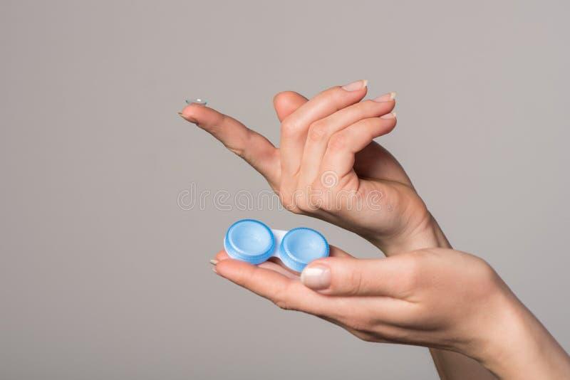 Lente de contato macia e recipiente azul nas mãos fêmeas no fundo cinzento fotografia de stock royalty free