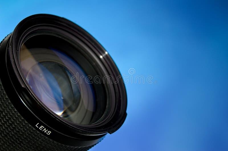 Lente de la fotografía sobre azul foto de archivo libre de regalías