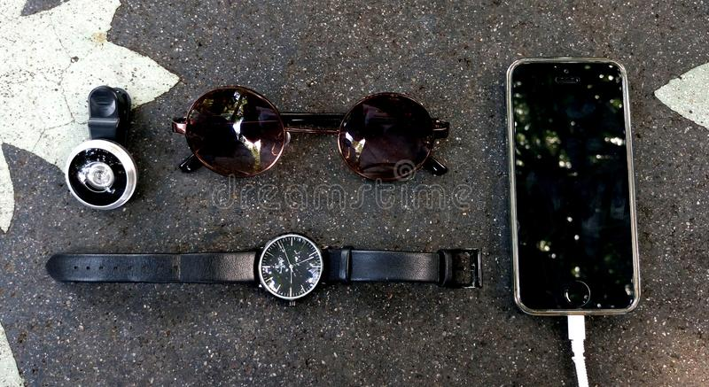 Lente de ojo de pescados, reloj, Sunglass, teléfono en la tabla de piedra fotos de archivo