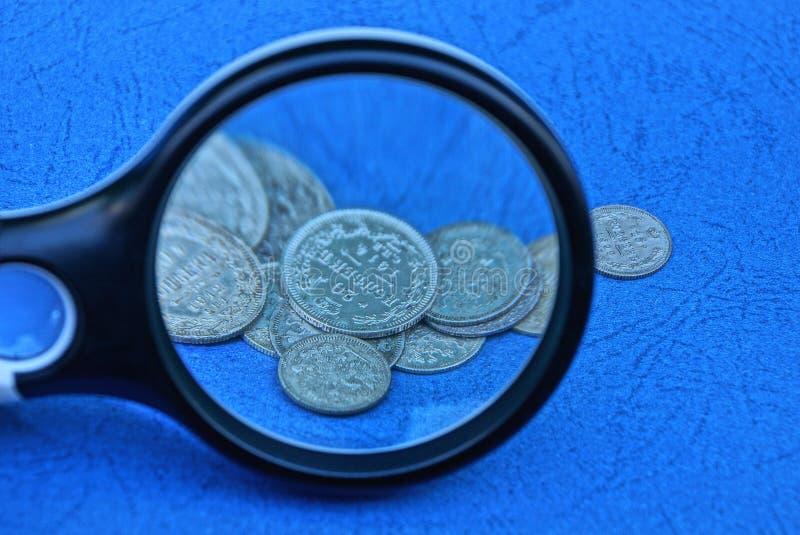 Lente di plastica e un mazzo di vecchie monete d'argento su una tavola blu fotografia stock