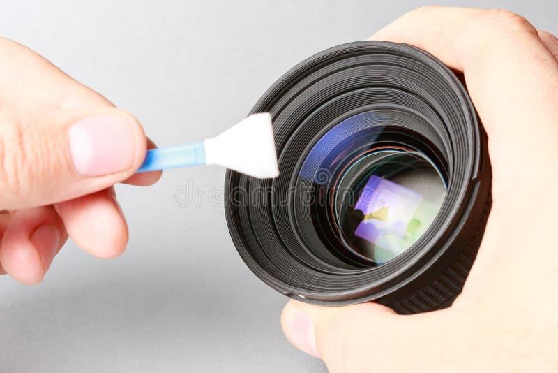 Lente a disposición, una mano que sostiene la lente que cepilla en segundo lugar con un especial foto de archivo