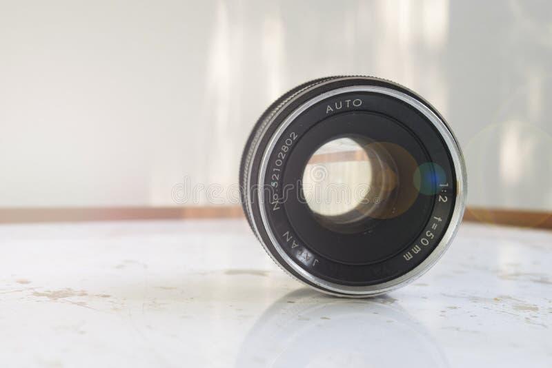 lente do vintage de 50mm com um alargamento e luzes suaves em uma tabela do grunge foto de stock royalty free