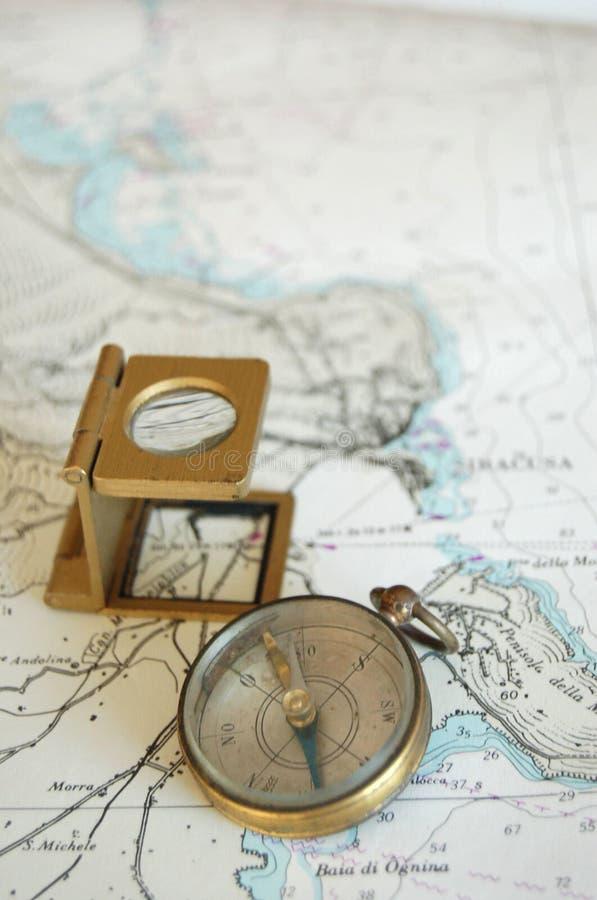 Lente e compasso em um mapa! imagem de stock