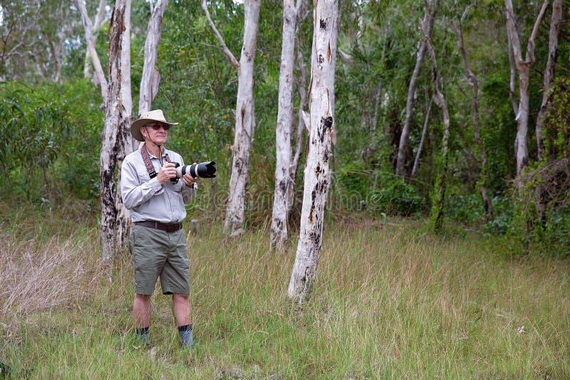 Lente longa de Holding Camera And do fotógrafo em Bushland imagens de stock royalty free