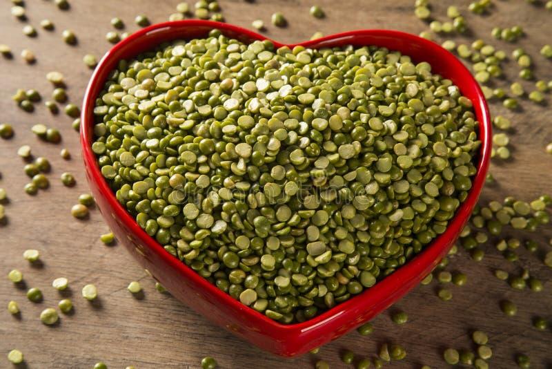 Lentejas verdes dentro de un pote del corazón en el fondo de madera Pulsos crudos comestibles de la familia de legumbre fotografía de archivo libre de regalías