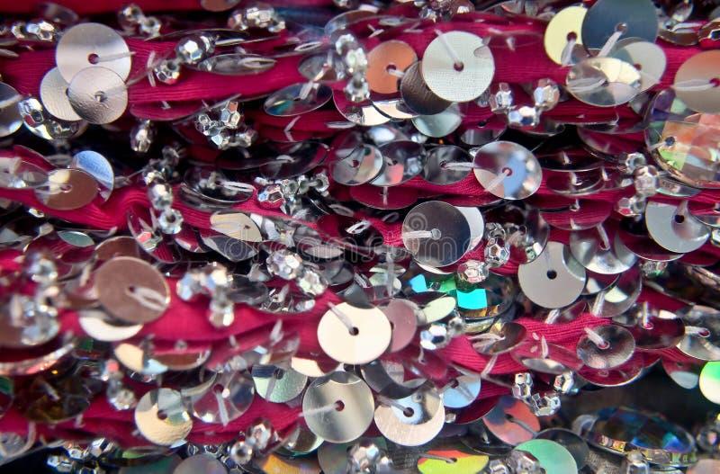 Lentejuelas redondas coloridas en la tela que hace punto para los fondos del día de fiesta foto de archivo