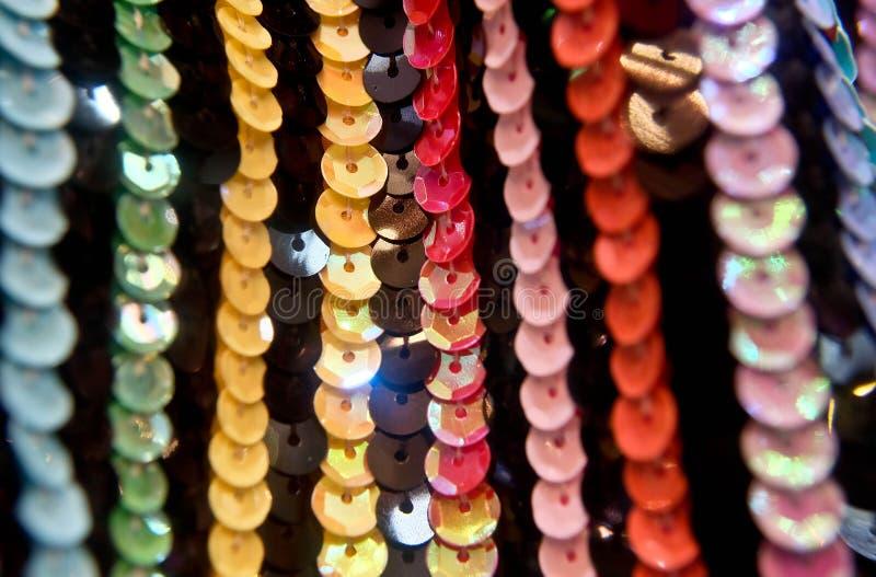 Lentejuelas redondas coloridas en la tela que hace punto para los fondos del día de fiesta imagen de archivo
