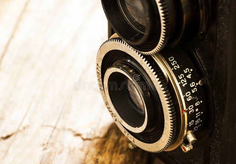 Lentes antigas, velhas da câmera dois da foto no fundo de madeira rústico da castanha fotografia de stock
