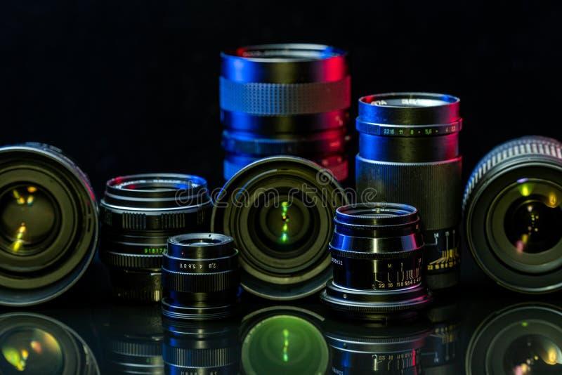 Lentes antiguas y modernas para la cámara con fondo negro imagenes de archivo