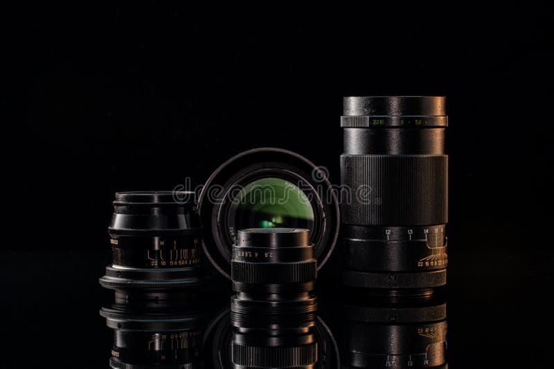 Lentes antiguas y modernas para la cámara con fondo negro foto de archivo