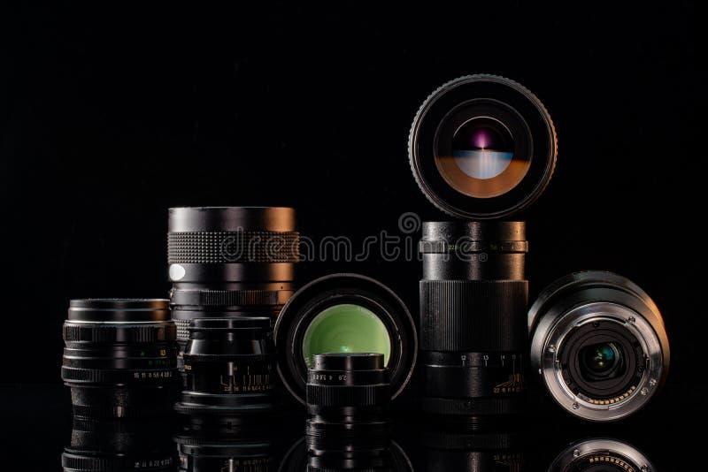 Lentes antiguas y modernas para la cámara con fondo negro imágenes de archivo libres de regalías