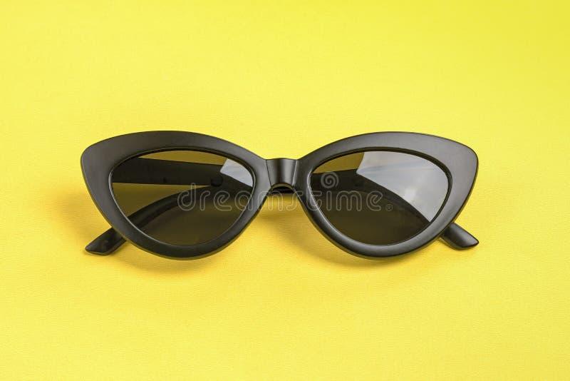 Lentes de sol negros elegantes aisladas en fondo amarillo imágenes de archivo libres de regalías