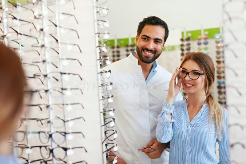 Lentes de With Woman Choosing del oculista en la tienda de los vidrios fotografía de archivo