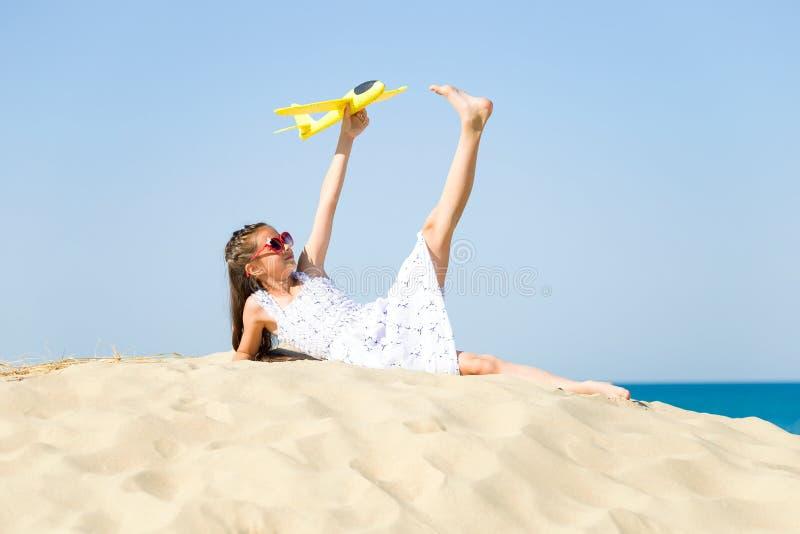 Lentes del sol de la niña que llevan feliz linda y un vestido blanco que miente en la playa arenosa por el mar y el playi fotos de archivo