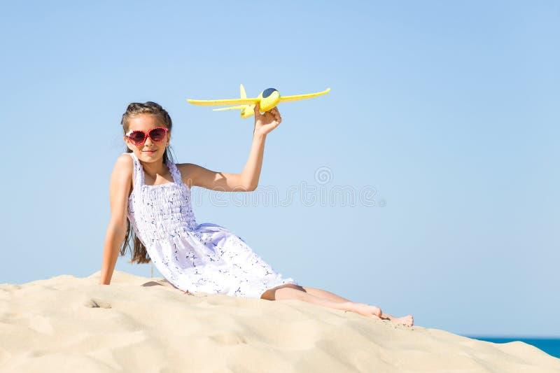 Lentes del sol de la niña que llevan feliz linda y un vestido blanco que se sienta en la playa arenosa por el mar y el pla imagenes de archivo