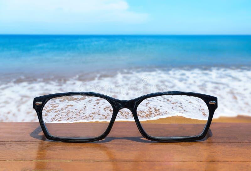 Lentes en el frente de madera de la tabla del fondo tropical del mar foto de archivo libre de regalías