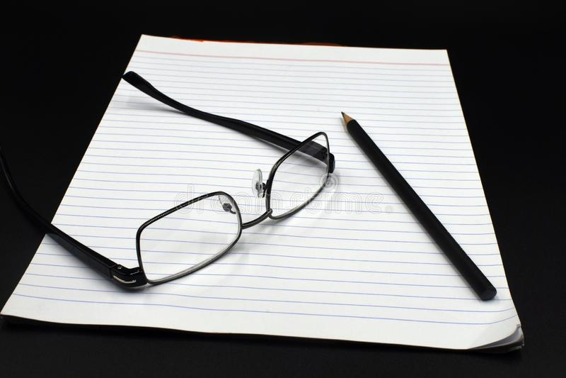 Lentes en una libreta con un lápiz y un fondo negro foto de archivo libre de regalías