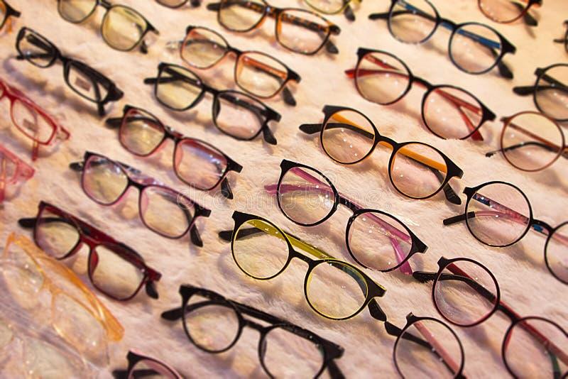 Lentes en venta en la amplia selección de lentes con la protección ULTRAVIOLETA y gafas en colores variados y estilos Ventas y gr imagen de archivo