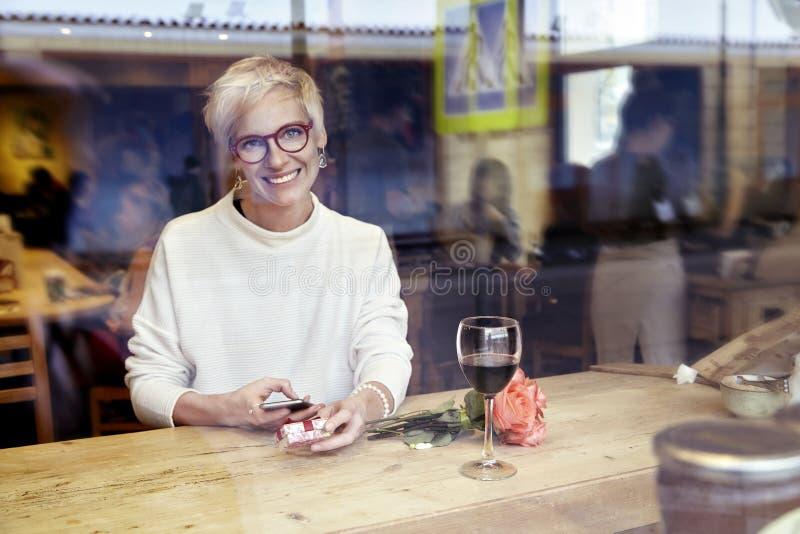Lentes que llevan de la mujer rubia hermosa que miran a la cámara, usando el teléfono móvil en café Consiguió un mensaje del amor fotografía de archivo libre de regalías