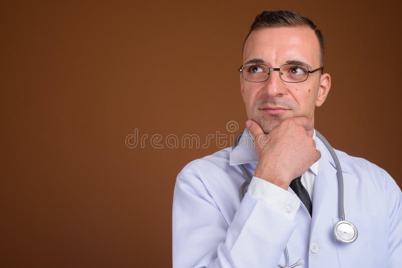 Lentes que llevan del doctor del hombre contra fondo marrón fotos de archivo libres de regalías