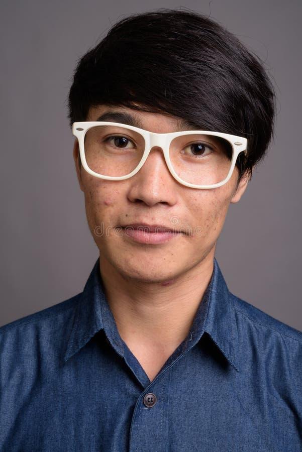 Lentes que llevan del hombre asiático joven que parecen elegantes contra vagos grises imágenes de archivo libres de regalías
