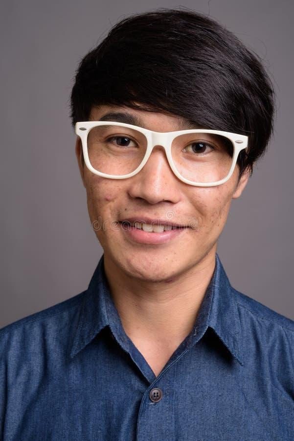 Lentes que llevan del hombre asiático joven que parecen elegantes contra vagos grises fotografía de archivo libre de regalías