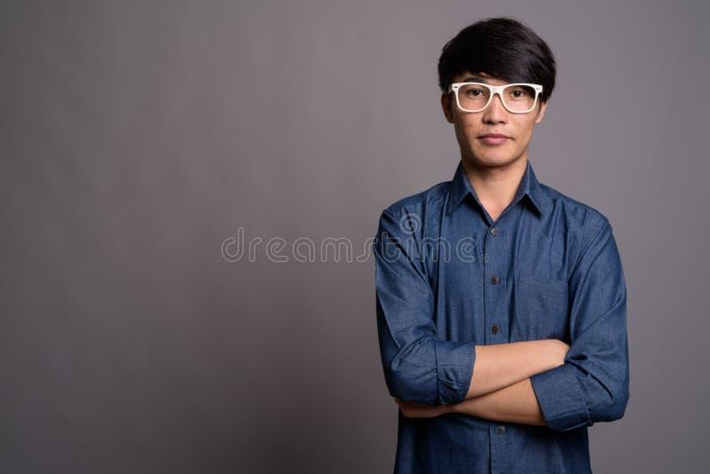 Lentes que llevan del hombre asiático joven que parecen elegantes contra vagos grises imagen de archivo libre de regalías