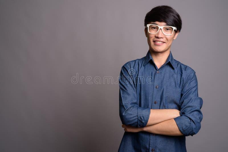 Lentes que llevan del hombre asiático joven que parecen elegantes contra vagos grises foto de archivo libre de regalías