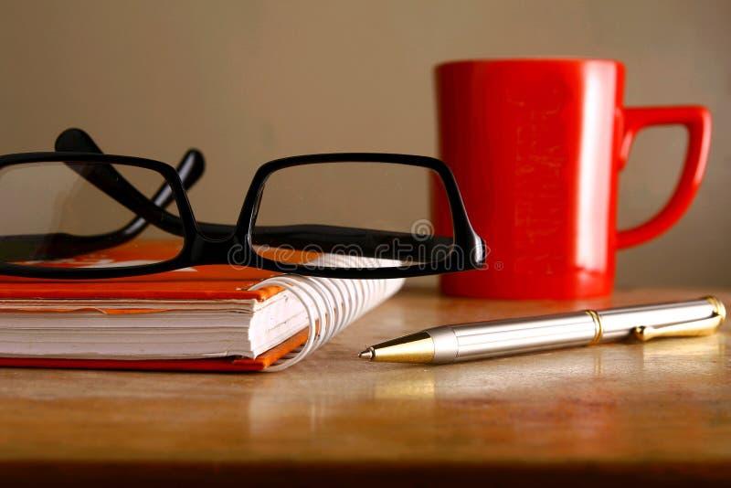 Lentes, taza de café, cuaderno y una pluma foto de archivo