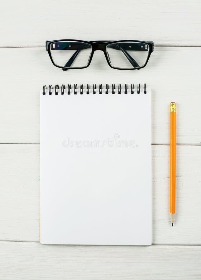 Lentes y libreta con el lápiz en una tabla de madera blanca, visión vertical, superior imágenes de archivo libres de regalías