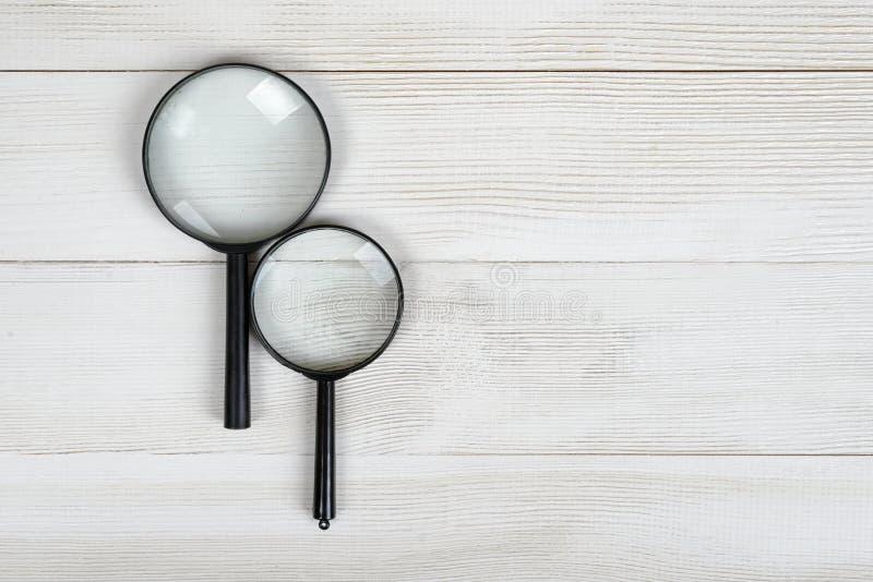 Lenti d'ingrandimento che si trovano su una superficie di legno con spazio aperto nella vista superiore fotografia stock libera da diritti